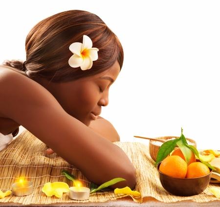 hair spa: Foto de mujer encantadora africano con los ojos cerrados y la flor blanca Franjipani en la cabeza relajada sobre la mesa de masajes en el sal�n de spa de lujo, disfrutando de dayspa, estilo de vida saludable, tratamientos de belleza, el concepto de cuidado del cuerpo