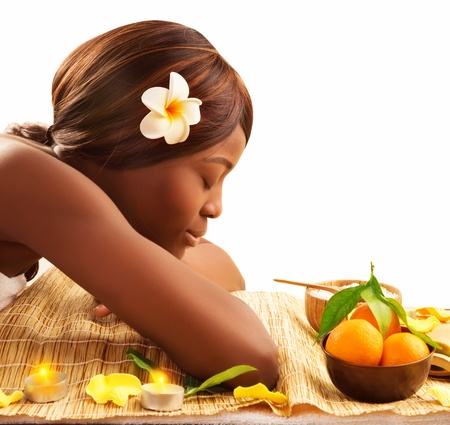 visage femme africaine: Photo d'une femme africaine belle avec les yeux ferm�s et blanc de fleurs Franjipani en t�te d�tendue sur la table de massage dans le salon de spa de luxe, b�n�ficiant dayspa, mode de vie sain, soins de beaut�, concept cocooning