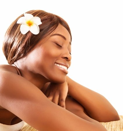 Picture of beautiful African woman with closed eyes enjoying dayspa, attractive female lying down on massage table with franjipani flowers in dark hair, luxury spa salon, beauty treatment