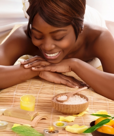 body spa: Photo of attractive african woman on massage table in luxury spa salon, smiling female enjoying spa therapy, alternative medicine, white franjipani flower in dark hair, beauty salon, pampering concept
