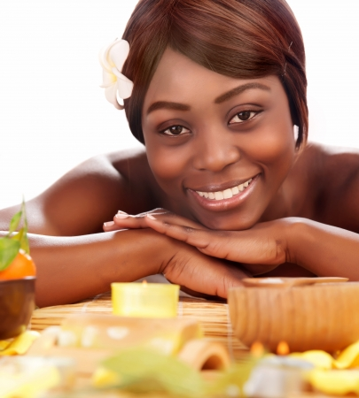 Image of beautiful afro female with franjipani flower in head enjoying dayspa, american woman relaxed in luxury spa salon, skin care, healthy lifestyle, pampering, vacation and wellness concept  photo