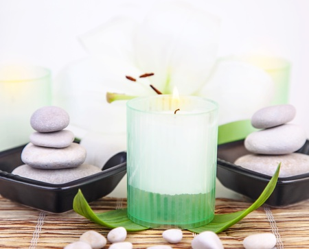 natural therapy: Picture of pebble stones in black plate, white lily flower, fresh green leaves, candle on wooden table in spa salon, aroma therapy, zen balance, luxury spa resort, natural cosmetic, relaxation concept
