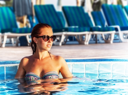 Image of beautiful woman in pool, pretty female taking sun bath in poolside, sexy girl wearing stylish sunglasses and colorful swimwear, luxury beach resort in hotel, tropical vacation, travel concept photo