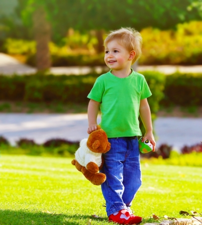 Photo of cute small boy in the park holding teddy bear, adorable child play with soft toy outdoors in spring time, sweet toddler having fun on backyard in sunny day, happy childhood concept photo
