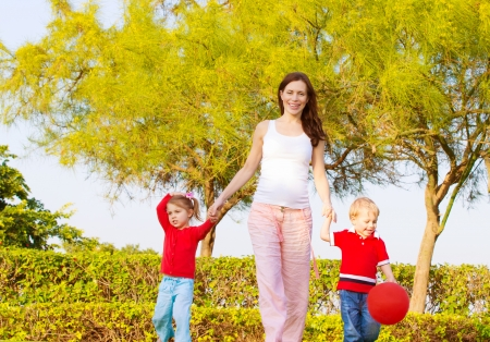 mother and son: Picture of happy young family in park, cute pregnant mother with two sweet child walking outdoors in spring time, beautiful woman with son and daughter having fun on backyard, love and happiness