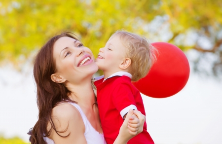 Image of cute little boy kissing mom, beautiful brunette woman with adorable child having fun outdoor in spring time, small kid with red balloon enjoying summer holiday, happy family, love concept photo
