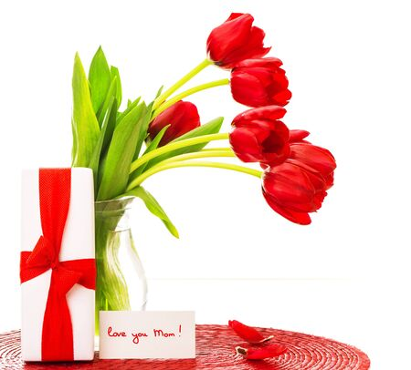 Photo of beautiful red tulips bouquet in vase, white giftbox with ribbon, greeting card, love you mom, happy mothers day, flowers bunch as present, romantic still life, merry holiday, love concept  photo