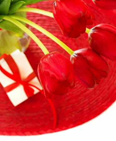 Picture of beautiful red tulip flowers in glass vase with small white present box on the table, romantic still life, happy mothers day, luxury greetings, special occasion, gift for birthday photo