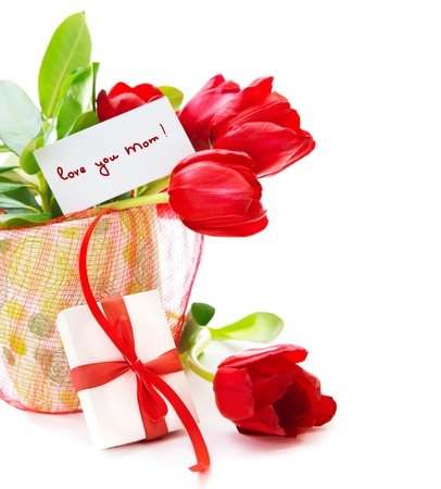 Photo of red tulips flower in pot with greeting card on fresh green leaves and gift box isolated on white background, romantic still life, happy mothers day, spring season, romance and love concept photo