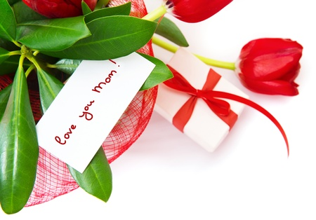 Picture of red tulips flower with greeting postcard on fresh green leaves and gift box isolated on white background,festive border, happy mothers day, spring season, romance and love concept photo