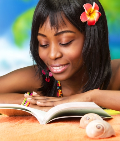 Photo of beautiful african woman read book on the beach, pretty black female enjoying summer vacation, cute young lady with red flowers in dark hair taking sunbath, happy lifestyle, luxury resort
