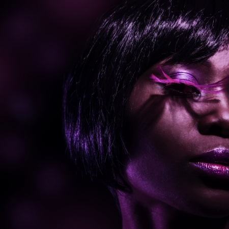 salon background: Photo of beautiful black woman with fashionable pink eyelashes isolated on dark background, half face, stylish makeup, female with gorgeous short haircut, luxury beauty salon, vogue concept