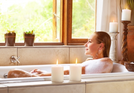 lying in bathtub: Picture of beautiful woman taking bath at home, cute female lying down in bathtub, warm candle light, romantic atmosphere, pampering and hygiene, spa resort in hotel, zen balance concept  Stock Photo