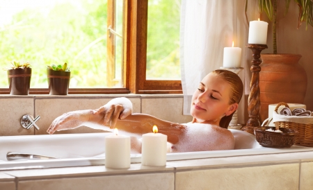 women bathing: Photo of sensual woman in bathtub relaxed, female in jacuzzi, skincare and hygiene, aroma candle, taking bath, luxury spa resort, girl enjoying bathing with soap foam, vacation and holiday concept Stock Photo