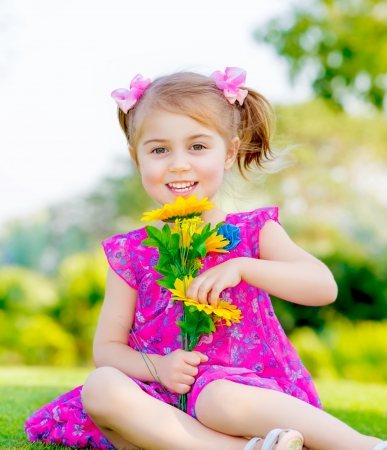 cute child holding fresh sunflower flowers photo