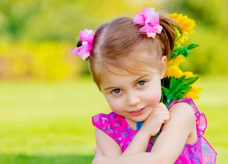 baby girl playing: cute child holding fresh sunflower flowers