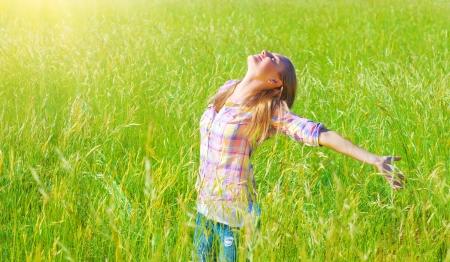 manos levantadas: Mujer que tiene diversión al aire libre, disfrutando del aire fresco y la hierba verde de la primavera, la libertad y la felicidad concepto