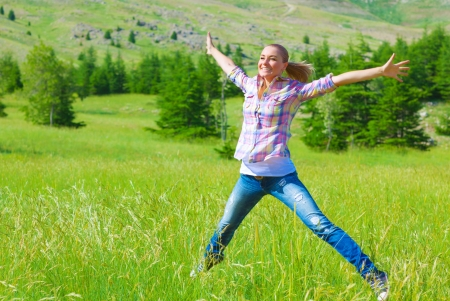Happy girl jumping on the field, enjoying fresh air and spring green grass, freedom and happiness concept