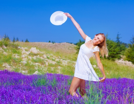 Cute girl dancing on lavender field, beautiful happy woman enjoying purple floral glade, pretty cheerful young lady walking on flower meadow, smiling female raised up hands with white hat in blue sky photo