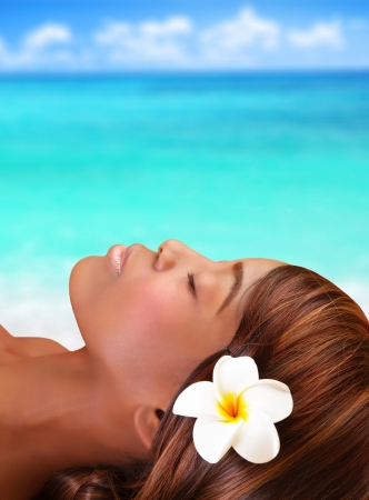 Beautiful black woman lying down with closed eyes on the beach, day spa, summertime vacation photo