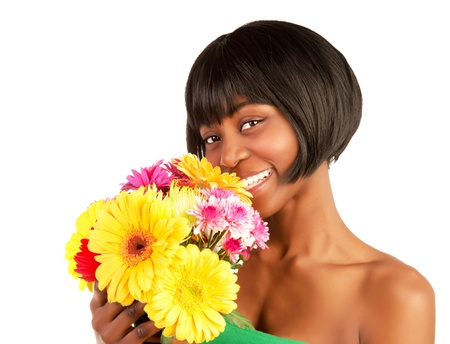 Closeup portrait of gorgeous female with black skin holding in hands great colorful gerber flowers photo