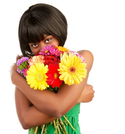 Beautiful african woman holding in hands and smelling big colorful bouquet of flowers, isolated on white background photo