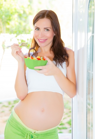 outdoor eating: Beautiful pregnant woman eating salad, healthy lifestyle, young mother, female awaiting for a baby