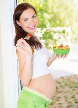 heathcare: Pretty young lady expecting baby, new life, pregnant female eating tasty sweet fruit salad, happy motherhood concept Stock Photo