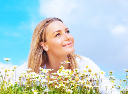 girl looking up: Beautiful woman enjoying daisy field and blue sky, nice female lying down in the meadow of flowers, pretty girl relaxing outdoor, happy young lady and green spring nature in harmony Stock Photo