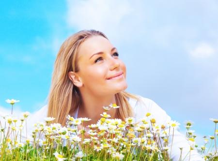 jolie fille: Belle femme appr�ciant le domaine de marguerite et le ciel bleu, belle femme couch�e dans la prairie de fleurs, jolie fille d�tente en plein air, heureux jeune femme et la nature de printemps vert en harmonie