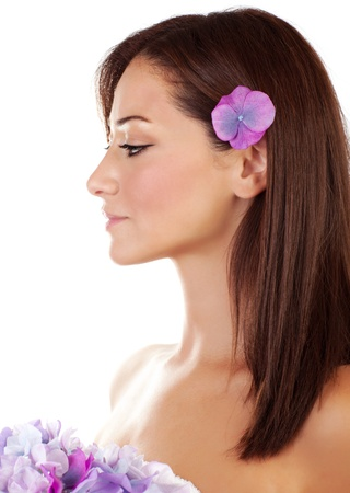 Beautiful brunette sensual woman enjoying day spa, side view of attractive young female with purple flowers isolated on white background  photo