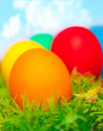 Beautiful painted colorful eggs on fresh green grass over blue sky, happy Easter holiday, religious traditions, spring nature  photo