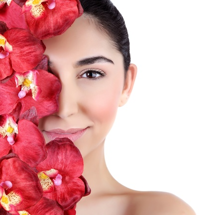 spa beauty: Beautiful young woman with fresh red orchid flowers on half of face isolated on white background, luxury spa salon