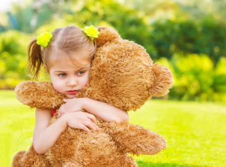 Little cute sad girl holding in hands brown teddy bear, upset child spending time outdoors in spring time