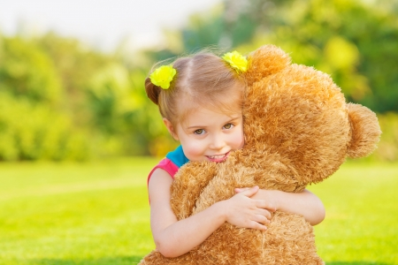 teddybear: Pretty girl playing with soft toy outdoor, cute infant having fun on backyard in spring time, happy childhood concept
