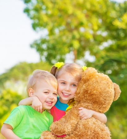 toy bear: Two happy children enjoying big brown soft bear outdoors, brother and sister hugging, having fun on spring time, love and happiness concept  Stock Photo
