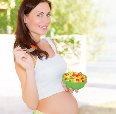 Closeup portrait of pretty woman awaiting baby eating fresh tasty sweet fruits, organic nutrition for pregnant girl, new life concept Stock Photo - 18737786