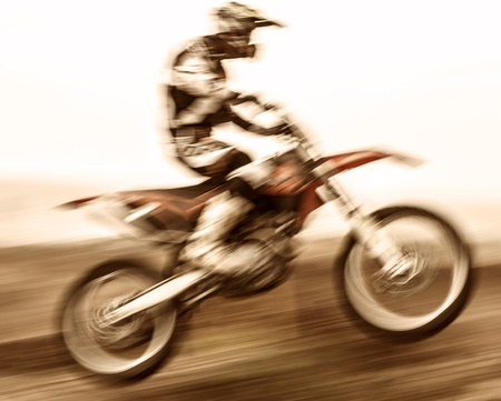 Extreme sport, slow motion on motorbike, pro race driver jumping on the dirt bike, motocross, speed and challenge concept photo