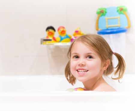 bathtub: Cute happy baby girl taking bath with foam and toys