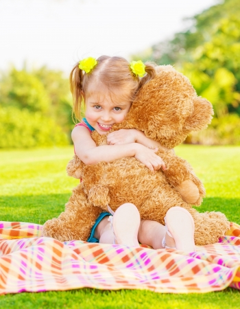 Cute little happy girl hugging big brown teddy bear and sitting down on green grass meadow, spring season Stock Photo