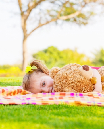 Adorable child resting on backyard in spring time, baby girl laying down on green field with teddy bear, having fun outdoors, happy childhood concept photo