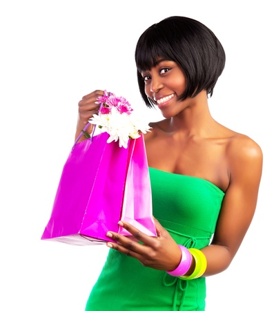 happy shopper: Beautiful smiling black woman with pink shopping bag isolated on white background, sale and money spending concept