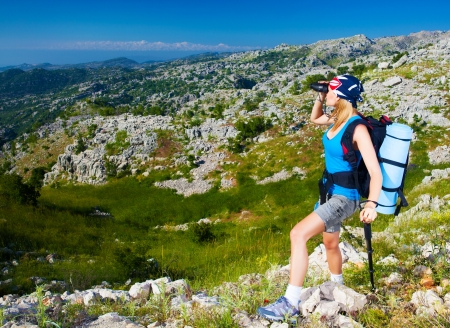 Young active female standing on the top of mountain and watching away in binocular, extreme lifestyle, traveling and trek concept photo