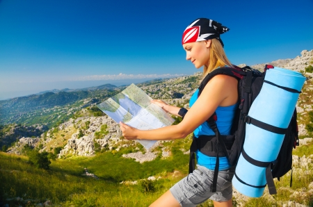 woman hiking: Young sporty woman standing on the peak on mountain watching on map, extreme adventure, happiness and freedom concept