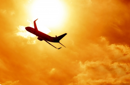 fly black: Silhouette of big airplane on beautiful orange sunset background, fast aerial transport, traveling and voyage concept  Stock Photo