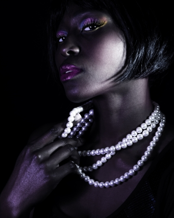 Closeup portrait of gorgeous African woman isolated on black background, elegant white pearl beads, stylish makeup, luxury beauty salon