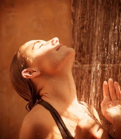 mujer bañandose: Primer plano de una hermosa mujer sexy tomar una ducha al aire libre de mujeres, con los ojos cerrados disfrutando de la caída de gotas de agua y el brillo del sol, el bienestar y el concepto de placer Foto de archivo