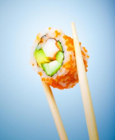 comida japonesa: Rollo de sushi sabroso con cangrejo, pepino, aguacate y caviar rojo en palillos aislados en fondo azul, comida japonesa tradicional