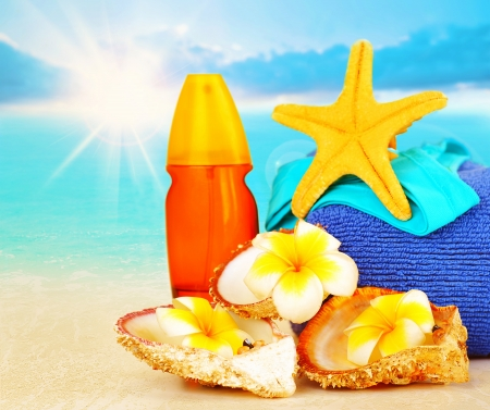 Beach items on sandy coast over blue sea background, sunscreen, yellow starfish, seashell, frangipani flowers, travel and vacation concept photo