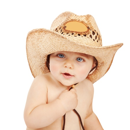 Cute baby boy wearing big cowboy hat isolated on white background, adorable child having fun indoors, happy childhood